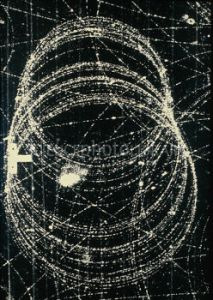 ^BElectron and positron^b spiral tracks seen in a cloud chamber at the Lawrence Berkeley Laboratory, California. The electron and positron started their lives at the bottom of the frame; they were generated by a gamma ray entering from the right. The positron, which is an electron with a positive charge, spirals (larger loops) towards the bottom left corner while the electron's smaller loops move upwards. The other tracks crossing the frame are also due to electrons and positrons created by gamma rays beyond the right hand edge of the frame; the electrons curl clockwise while the positrons curl anticlockwise.
